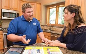 one of our plumbers explains to the client the costs of fixing the plumbing system